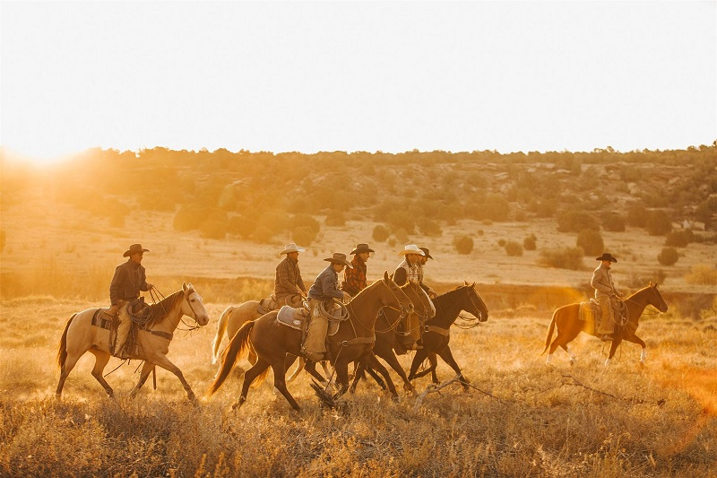 A group of cowboys riding across a pasture.