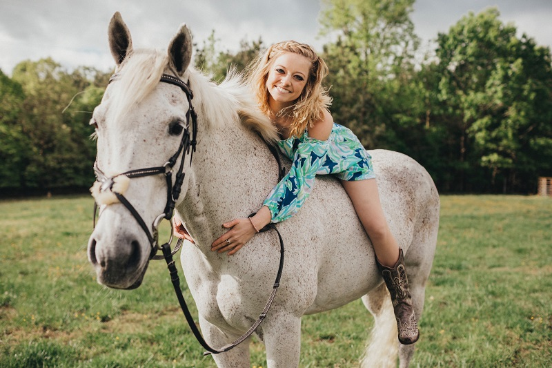 A girl in a blue dress lies on a white horse.