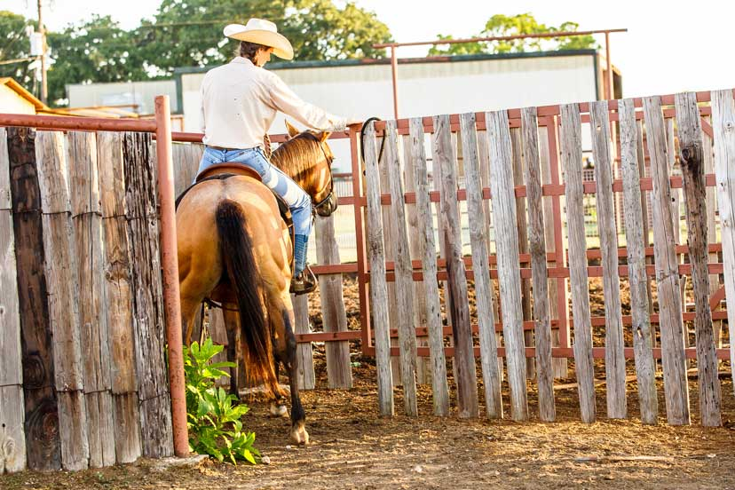 Britney Ferguson opens a gate while horseback on the Snodgress Cattle Co. ranch (Credit: Abigail Boatwright)