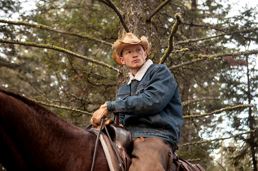 Jefferson White, who plays Jimmy Hurdstrom, sits astride a horse