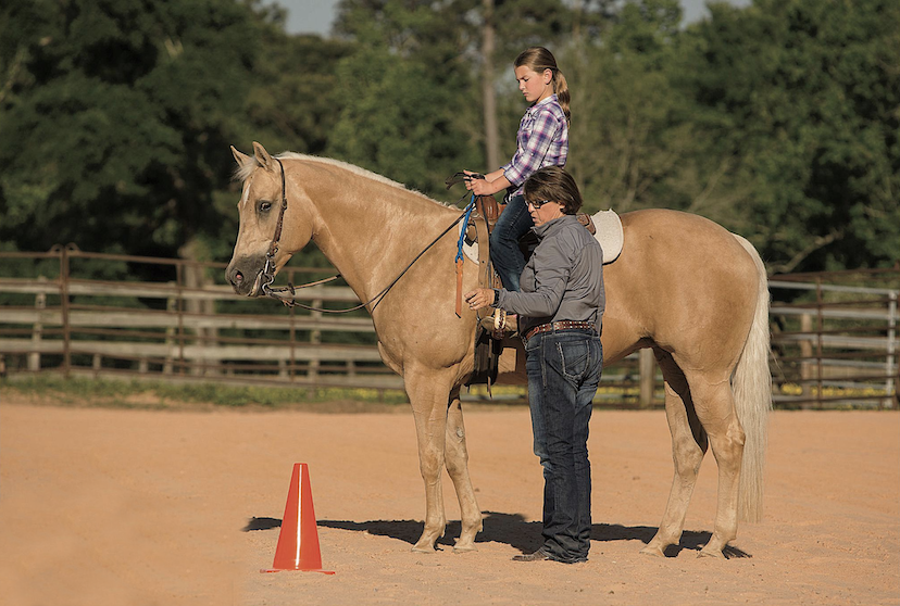trainer Sharon Wellman coaches a youth rider aboard a palomino Quarter Horse (Credit: Kate Bradley-Byers)