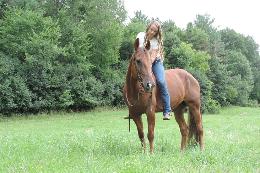 girl rides a chestnut horse bareback in a green pasture (Credit: courtesy of Adrianna Davidson)