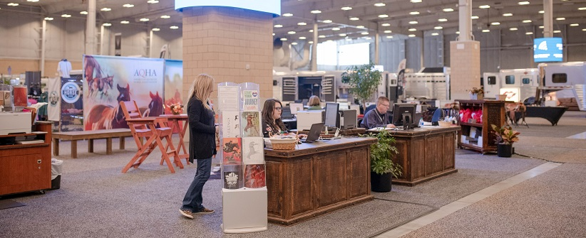 AQHA member experience representatives are working in the AQHA booth at wooden desks as a customer watches