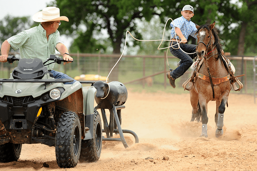 ATV pulls Perfect Calf roping dummy tracked by young roper on black horse