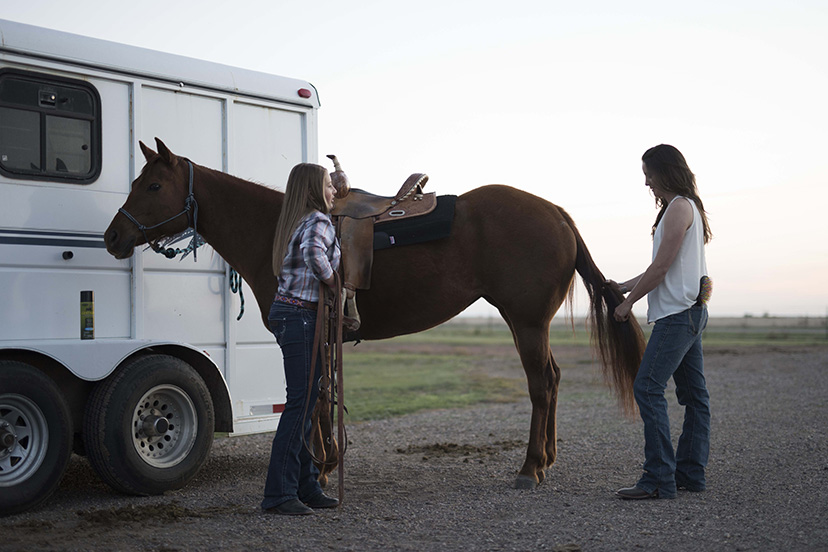 two girls wearing Wrangler jeans brush a horse that is tied to a horse trailer (Credit: AQHA)