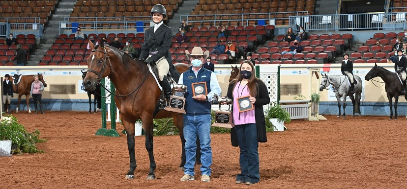 a woman on a bay horse in english attire stands with two people presenting awards in masks.