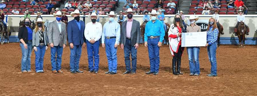 A line of people stand in an arena in masks to present a check to a girl.